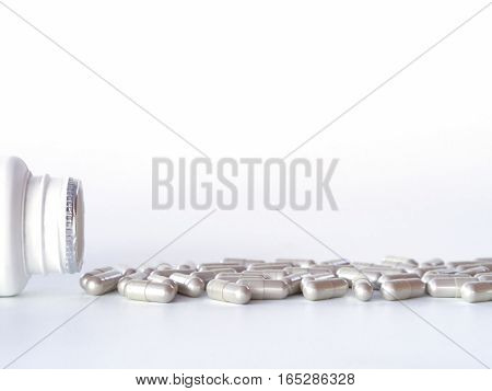 Pills Spilling Out Of The Bottle On White Background.