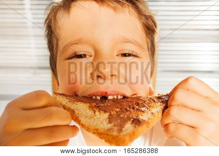 Close-up portrait of happy kid boy eating toast with chocolate spread