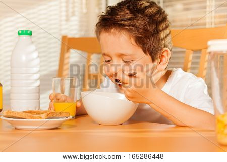 Close-up portrait of happy kid boy eating cereals with milk and drinking fresh orange juice