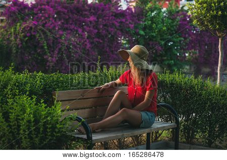 Young blond woman tourist in hat and red blouse sitting on bench surrounded by green bushes and looking aside on summer day at sunset, Alanya, Mediterranean region, Turkey