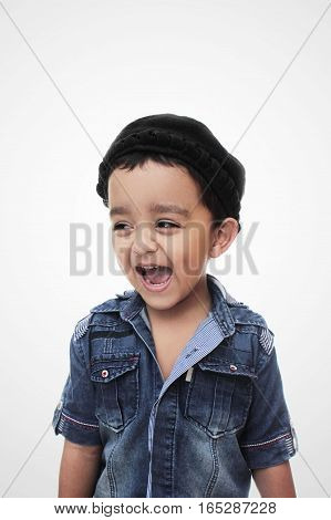 Portrait. happy little south asian boy wearing cultural hat. smiling and looking away from camera isolated on white
