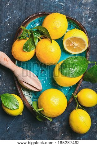 Close-up of freshly picked lemons with leaves in bright blue ceramic plate over dark blue shabby plywood background, top view, vertical composition