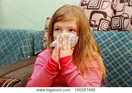 Little Girl Blows His Nose In A Paper Tissue