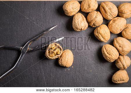 Walnuts with nutcracker on slate stone and a broken walnut
