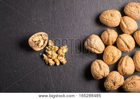 Walnuts isolated on slate stone with cracked walnut