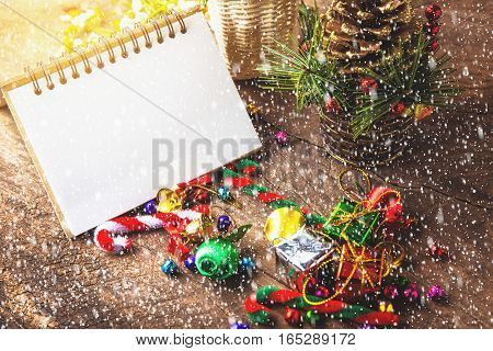Merry christmas and Happynew year text on blank notebook with snow gift box daisy flower candy ball and cane pine decoration on vintage wooden background.