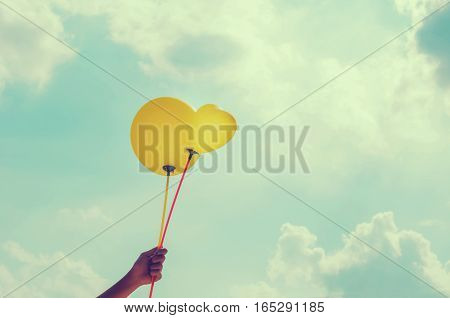 hand and balloon blue sky background and sunshine