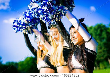 A team of pretty, female cheerleaders having fun outdoors.
