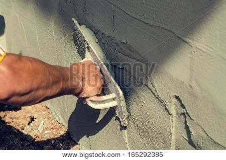 Construction worker holding plastering trowel smoothing wall defects