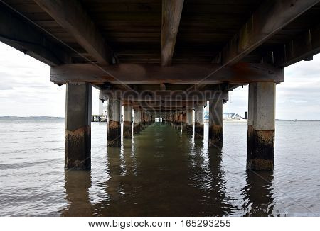 Under the wooden Pier at Rhyll (Philip Island Victoria Australia). Infinity view under the pier of weathered pilings.