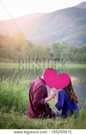 Loving couple. Beautiful young love couple holding paper hearts and smiling in outdoor nature vintage tone valentine concept.