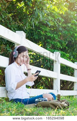 Young asian hipster wear headphone listening to music through smartphone standing outdoors on nature background.