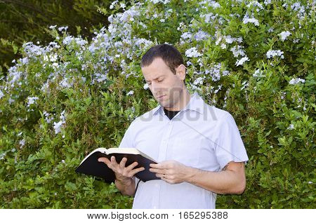 Man focused reading the Bible outside alone.