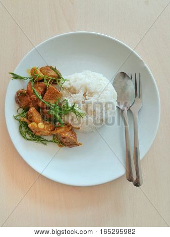 Rice and spicy pork cartilage with vegetable. Thai food on white dish.