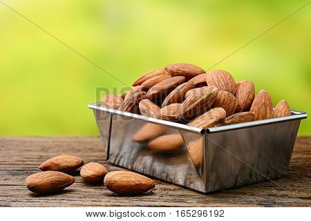 almonds on old wooden table with nature background