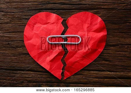 Paper broken heart with paperclips on wooden background