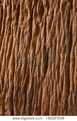 Old rough wood surface is pitted with cracks.