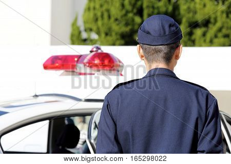 Back view of Japanese police officer with patrol car