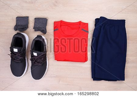 Set of running clothes on wooden background