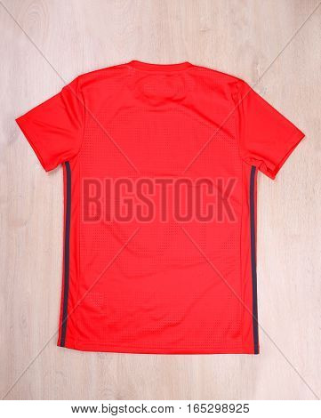 Red back sport tshirt on wooden background