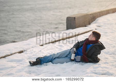 Man walking with a bottle of wine. He is dressed in winter coat scarf and gloves. Man was drunk. He lies on the snow on the quay. Winter depression.