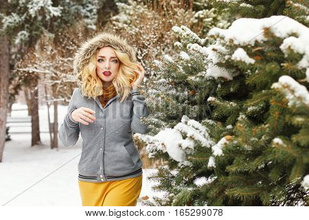 Lovely girl in a fur hood standing next to a tree in snow. Walking in a winter park.