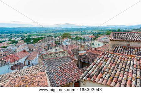 Terra cotta tiled roof tops of Corneilhan sit at different angles untidily stretch into the French countryside