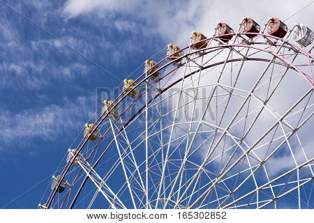 Close up large ferris wheel facing diagonally under blue sky
