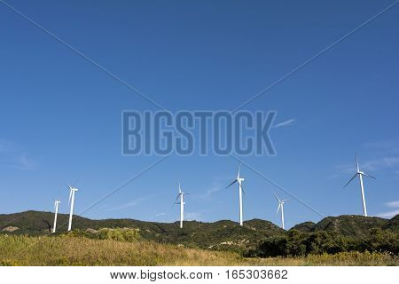 Several wind power plants under blue sky