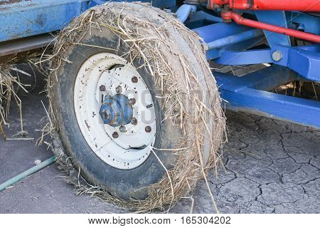 close up tyre of tractor full with straw after harvesting time