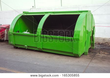 green large metal recycling dumpster Rusty old dumpster behind store.