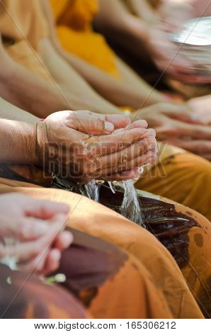 people celebrate Songkran festival (new year / water festival: 13 April) by pouring water into buddhist priest 's hand