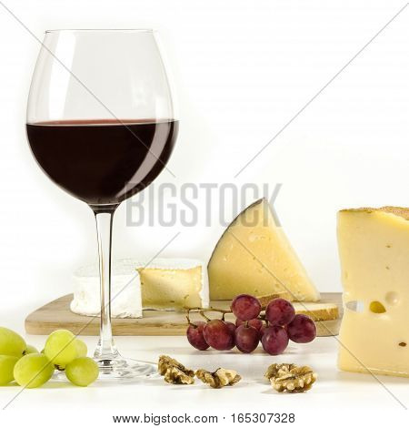 A square photo of a tasting with a glass of red wine, different types of cheese, nuts, and grapes, on a white background
