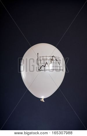 white balloon with a financial chart going down