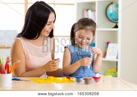child girl and mom play with color dough at home