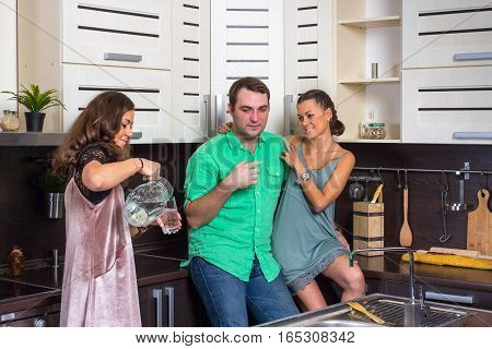 Happy hostess offers guests a glass of water in the kitchen
