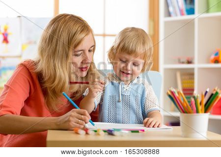 Woman teaching kid writing. Elementary pupil painting with teacher