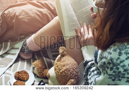 Girl Reading Book In Bed With Warm Socks Drinking Coffee