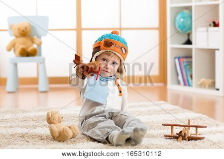 Happy kid playing with wooden toy airplane and teddy bear in nursery