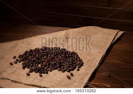 Coffee beans on sacking and wooden background
