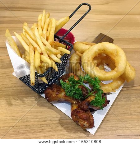 Fried chicken served with fried golden crispy onion ring and french fries decorated on a plate on wooden table