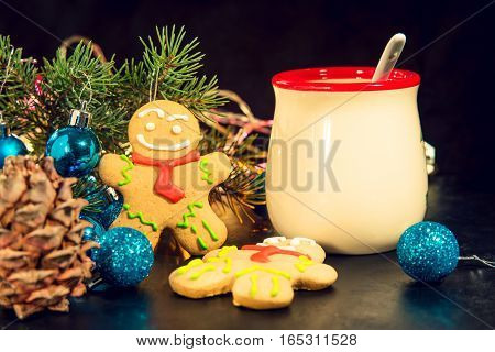 Gingerbread man near Christmas tree with toys and next to the Cup the concept of Christmas