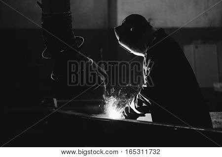 Worker At The Factory In The Helmet Is Of Iron In The Welding Process