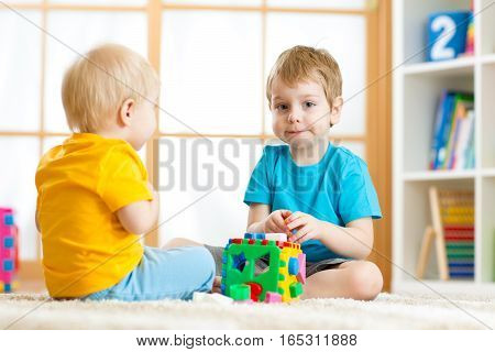 Children boys playing with logical educational toys, arranging and sorting shapes and sizes