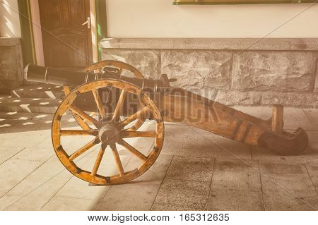 Old field cannon with wooden wheels. Retro toned photo