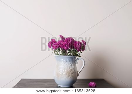 Pink chrysanthemum in a clay rarity vase on a wooden table light background