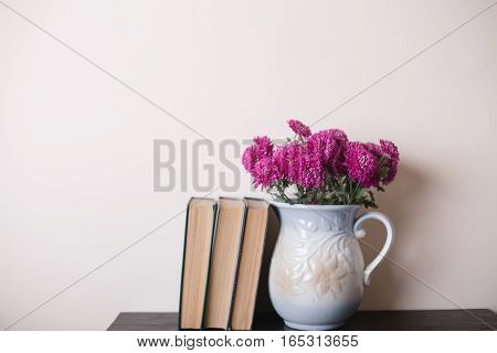 Pink chrysanthemum in a clay rarity vase and books on a wooden table light background