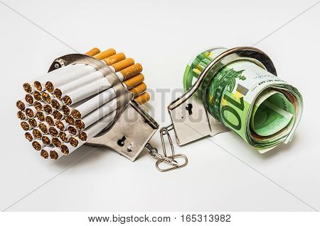 Cigarettes And Money With Handcuffs - Cost Of Smoking