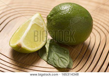 fresh green lemon and spearmint on wooden background