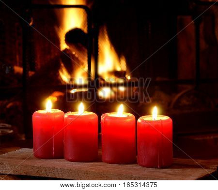 red candles in front of a fireplace